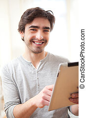 Young smiling man using a tablet