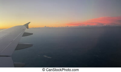 View of Airplane Wing in Sunrise Light above the clouds