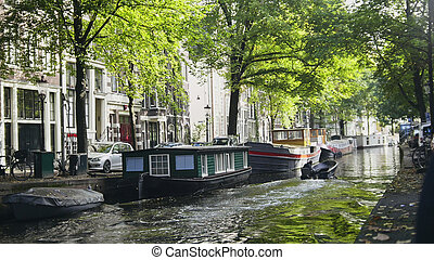 View of Amsterdam city: early morning, cloudy day, Autumn - cars and bicycles parked along the canal - Netherlands