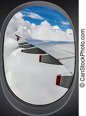 View of an airplane wing out the window from the seat inside a commercial jet airplane