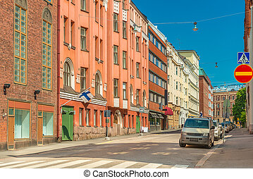 View of an empty street in Helsinki, Finland. Colored historical buildings with Finnish flags on the facades, parked cars and clear blue sky