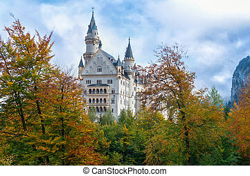 View of an old Neuschwanstein castle over autumn trees in the Alps in Germany with cloudy sky