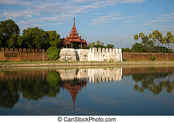 View of ancient gate and bastion of the Old city in the solar evening. Mandalay, Myanmar