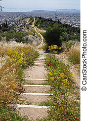 View of Athens Greece from Philoppapos hill of the muses. Crooked ancient trail distant city sea and sky horizon.