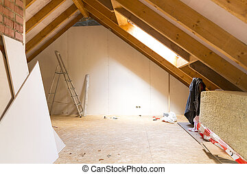 View of attic renovation and construction site with pile of...