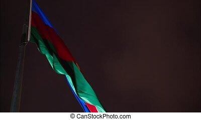 Azerbaijan flag floating in the wind against night sky