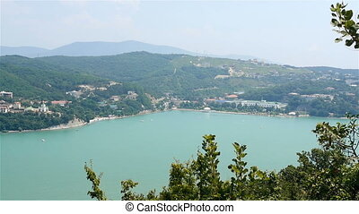 View of Azure Mountain Lake With A Settlement In The Hills Around It