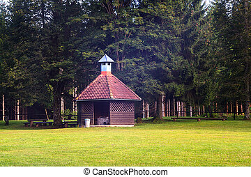 View of barbeque house on grass in front the trees