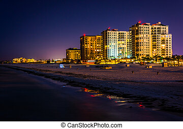 View of beachfront hotels and the beach from the fishing pier at night in Clearwater Beach, Florida.