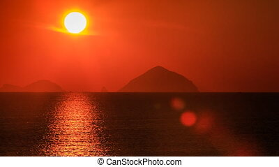panorama of enormous sun disk and sun-path across tranquil sea against defocused islands