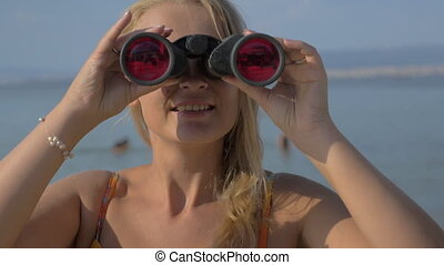 View of blond woman watching with binoculars against blurred sea