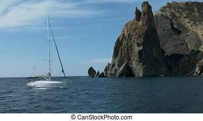 View of blue sea and sailing yacht in sunshine from other...