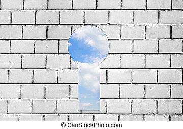 view of blue sky behind bw brick wall