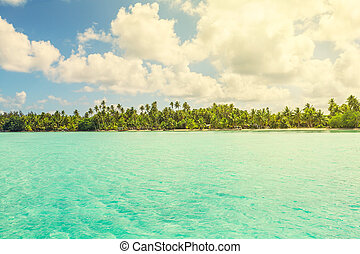 View of blue turquoise lagoon and far line of palm trees on translucent sunset light of Bora Bora island, French Polynesia