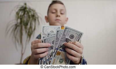 View of boy Counting Many American 100 bills. The little boy counts the American currency. White background, indoor