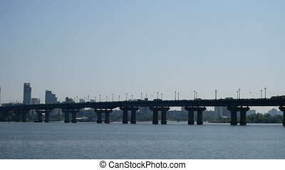 View of Bridge over the Dnipro river in Kyiv, Ukraine. Cars are moving along the bridge.