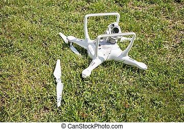 View of broken drone on grassy field