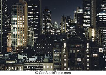 View of buildings in the Turtle Bay neighborhood at night,...