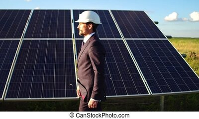 View of businessman walking along solar panels installed in the field.