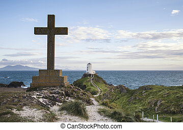 View of Celtic Cross on Angelsey with Twr Mawr Lighthouse in background landscape
