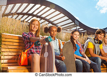 View of children who sit on wooden bench together
