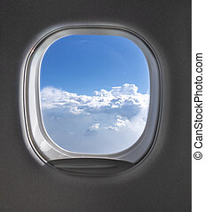 View of cloudy blue clear sky through airplane porthole.
