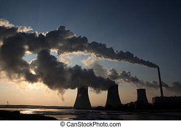 View of coal power plant against sun and huge fumes - View...