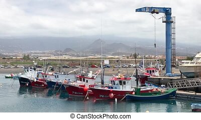 View of colorful boats moored in marina and mountains...
