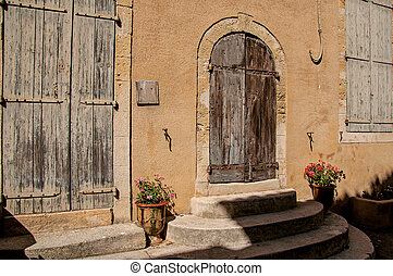 View of colorful house and door with flowers and steps, on a street of Lourmarin.
