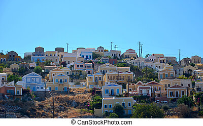 View of colorful houses on a hill in Simi island between Greece and Turkey in the Mediterranean with a mountain in the background under a clear blue sky