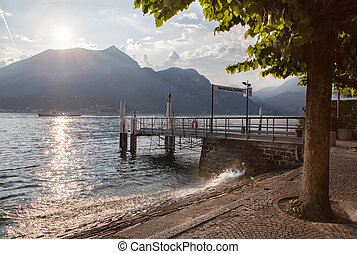 View of Como lake on sunset with pier in Italy