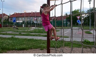 View of cute small girl climbs on a rope ladder at playground