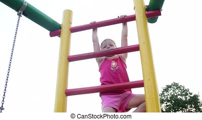 View of cute small girl climbs on a ladder at playground