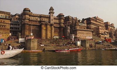 Medium, low-angle still shot of Darbhanga Ghat, boats, and people from the Ganges River, India