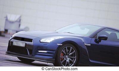 View of dark blue new car. Wheels. Presentation. Headlights. Automobile. Cold shades