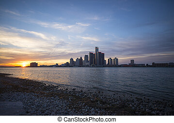 View of Detroit city skyline at sunset from the shore of the river