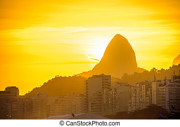 View of Dois Irmaos Mountain on the background of gold sunset from Copacabana beach, Rio de Janeiro, Brazil