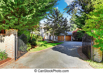 View of driveway with opened gate. Double garage and well kept garden. Northwest, USA