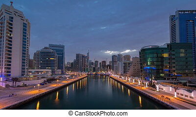 View of Dubai Marina Towers and canal in Dubai night to day timelapse