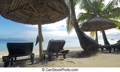 View of empty chaise-longue near native sun umbrella and palm trees against blue water, Mauritius Island