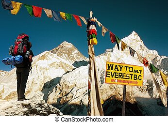 evening view of Everest with tourist and buddhist prayer flags from Kala Patthar, signpost and blue sky - way to Everest Base Camp - Nepal
