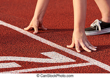 View of female athlete at race start. It stands on a red tartan track and is ready to fast run.