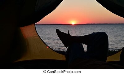 View of female legs in a tourist tent at sunset on the beach...