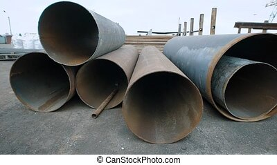 View of few rusty pipes arranged on junkyard of recycling...