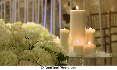 View of flowers and lighted candles on glass table