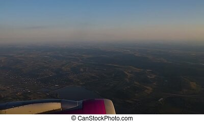 View of flying airplane engine through plane window.