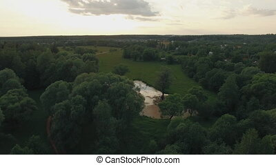 View of forest, lake and country houses against blue sky with sun and clouds in sunset at summer, Russia