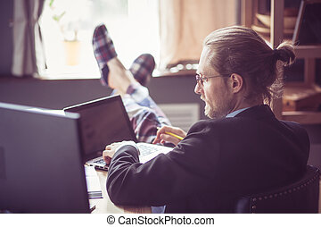 View of freelancer working at wooden desk. - Man working at...