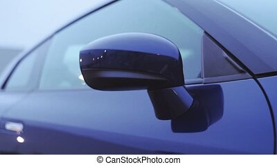 View of front mirror of new dark blue car. Presentation. Showing model. Automobile. Cold shades