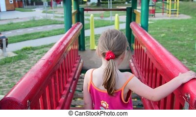 View of girl goes on rope bridge in the playset at playground